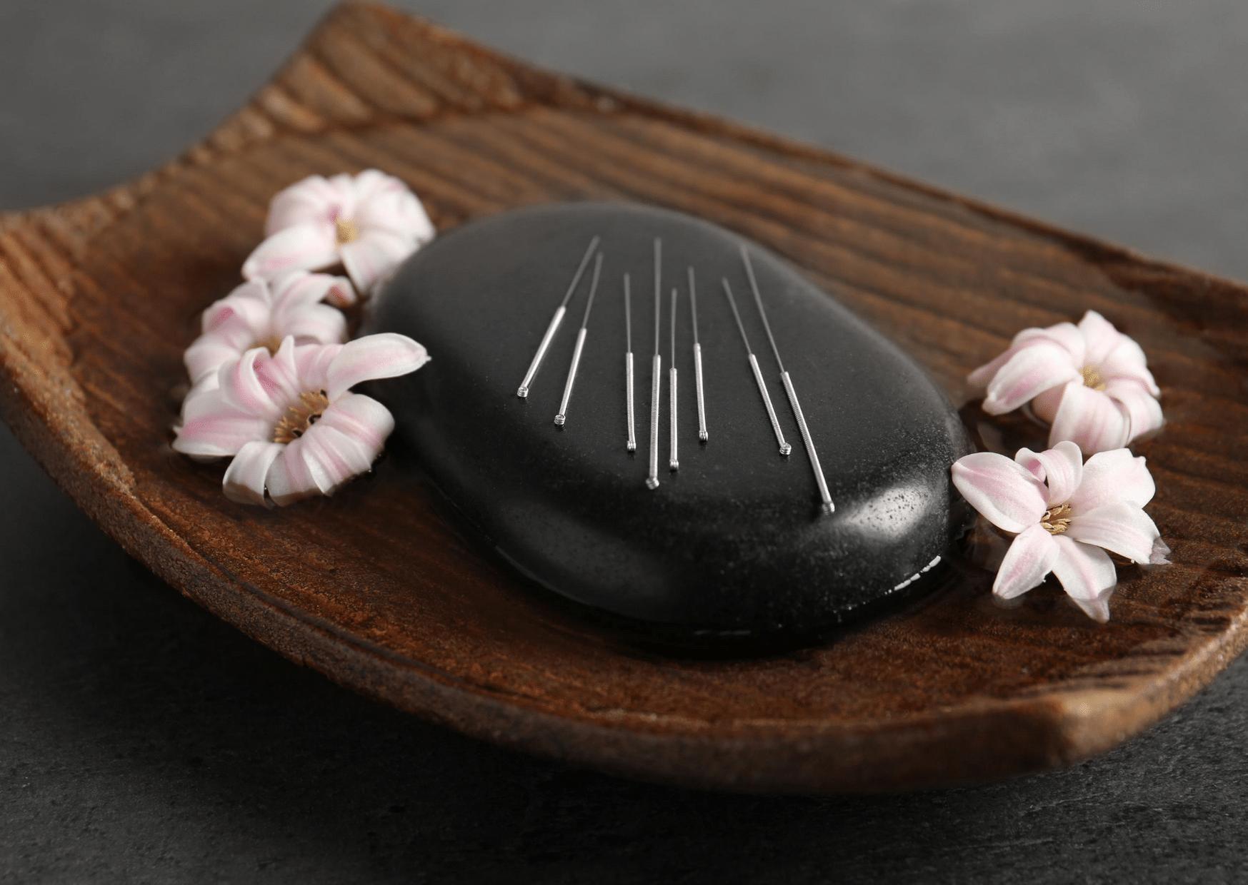 pierres de lave basalte dans bol marron entouré de fleurs pierre noire
