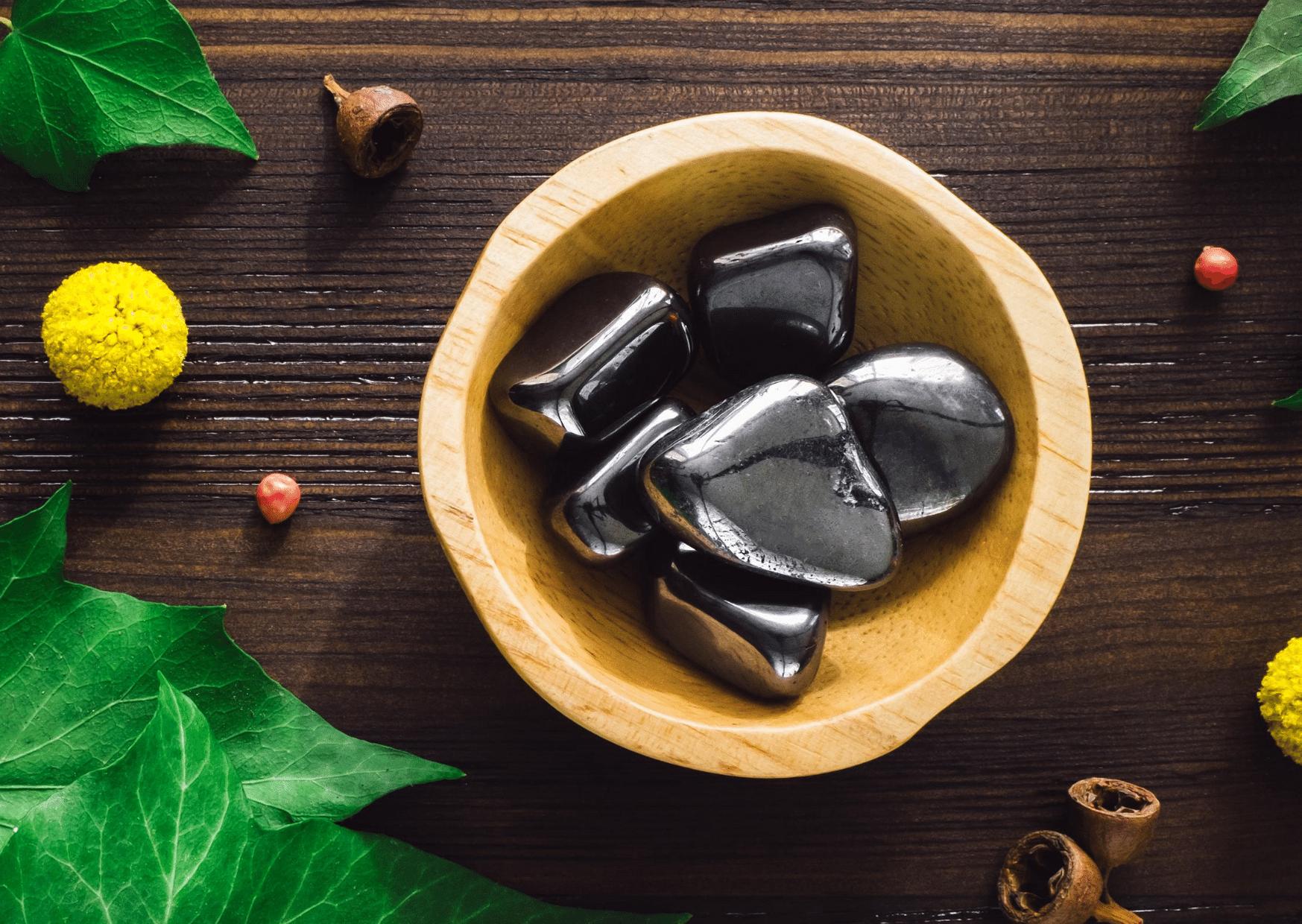 pierres hématite dans bol marron entouré de feuilles
