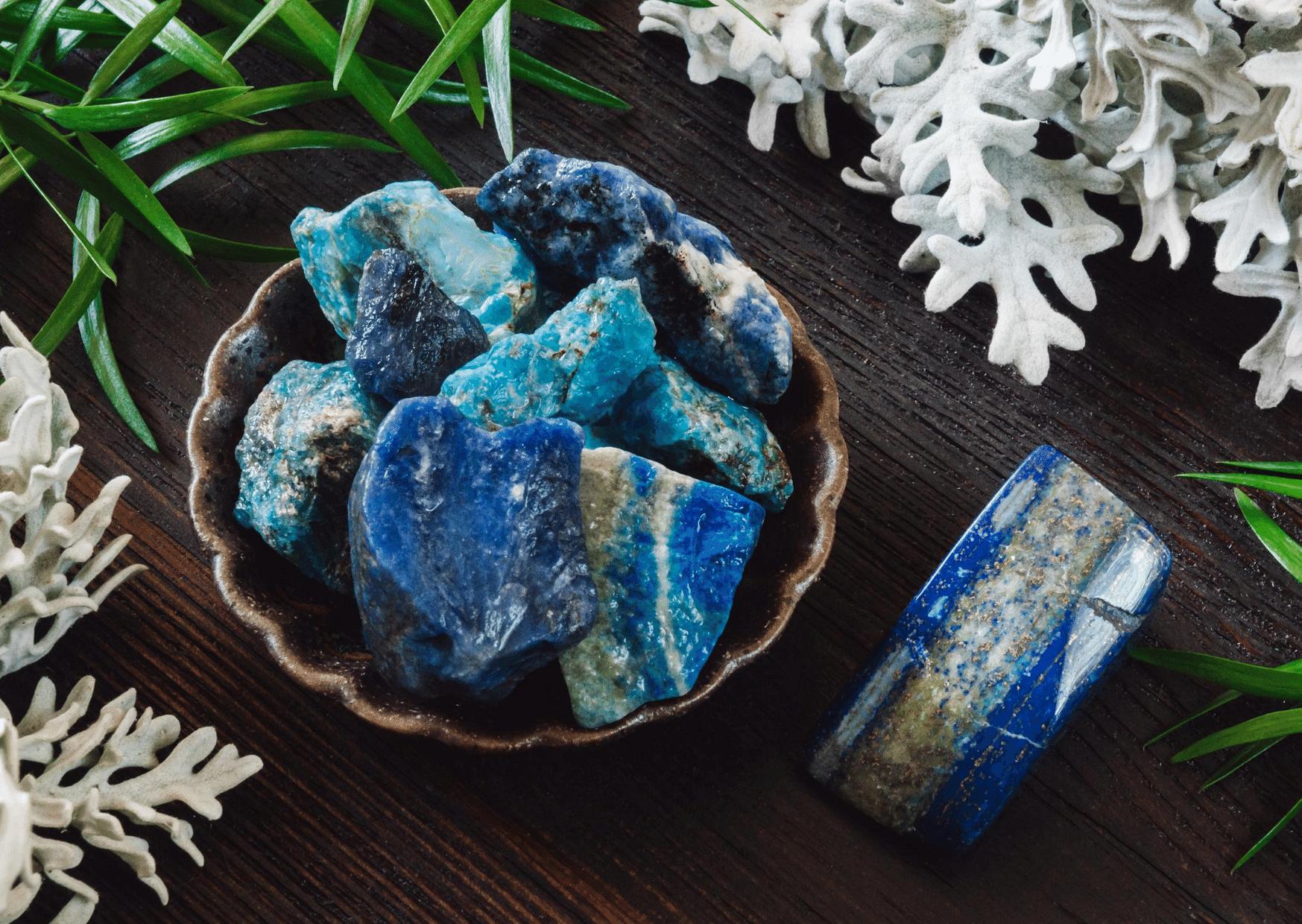 pierres lapis lazuli dans bol marron entouré de feuilles pierre bleu de lithothérapie
