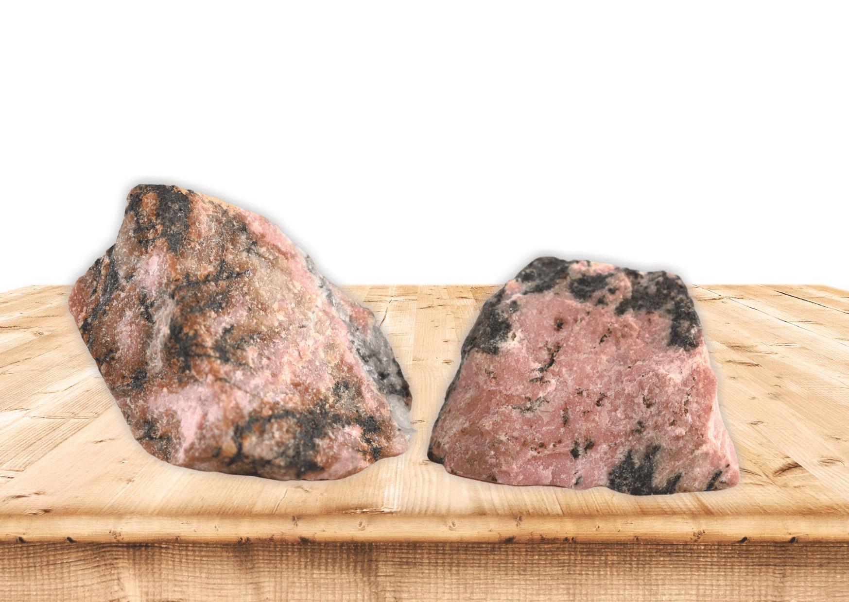 rhodonite pierre lithothérapie rose et noir brute possé sur table