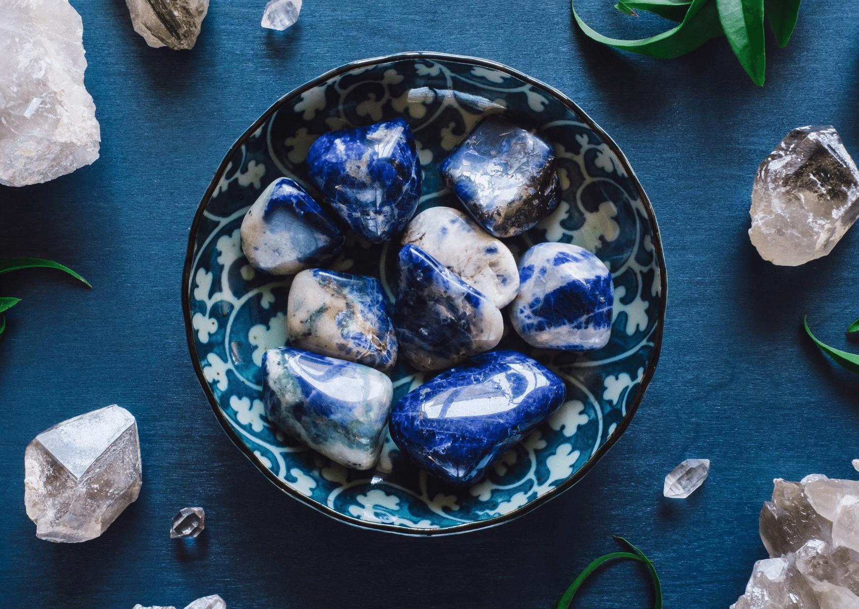 sodalite pierre lithothérapie bleu et blanche roulée possé sur table bleu entouré de plantes et cristaux